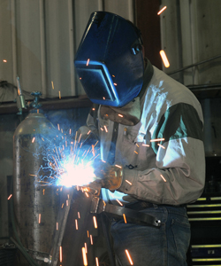 Torin Halsey/Times Record News    Antonio Rivas welds together a bracket during the fabrication of a heater unit at Chandler Manufacturing Inc. The company makes a variety of oil field equipment products.